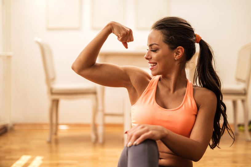 Happy athletic woman flexing her bicep at home.
